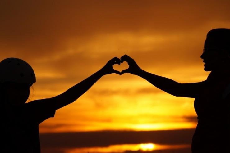 silhouette-of-mother-and-daughter-in-heart-shape-gesture-at-sunset